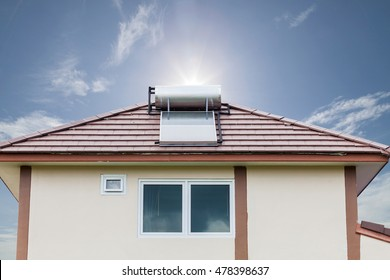 Solar panel for hot water system on roof on blue sky and sun background