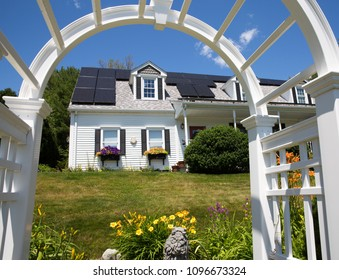 Solar panel installation on a nice cape cod house with sunny blue skies in the background