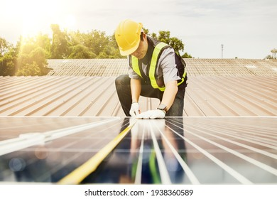 Solar panel installation work concept : Asian electrical engineer architects used a tape measure to measure the length of solar panels on the roof of an industrial factory.