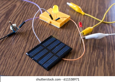Solar panel, led, breadboard, switch, alligator clip wire together for educational prototype. Electronic lesson at school