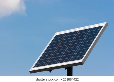 Solar panel mounted on a pole towards left against blue sky and white clouds.