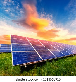 Solar panel on beautiful orange sundown background. Green grass and cloudy sky. Alternative energy concept