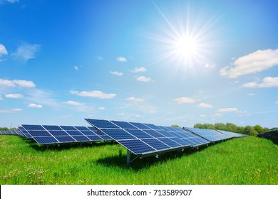 Solar panel on blue sky background. Green grass and cloudy sky. Alternative sun energy concept