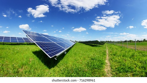 Solar panel on blue sky background. Green grass and cloudy sky. Alternative sun energy concept