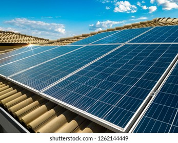 Solar panel on a red roof reflecting the sun and the cloudy blue sky in background
