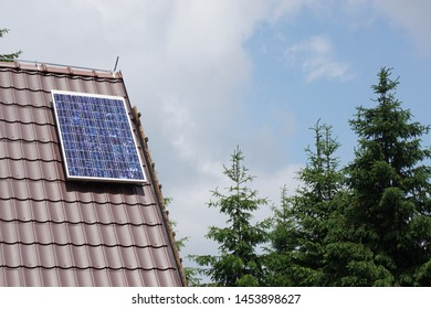 Solar panel on the roof. Blue cloudy sky. Pine trees in the background.
