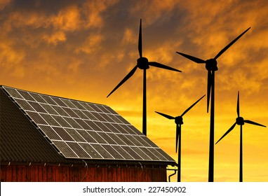 Solar panel on the roof of the house in the background wind turbines at sunset.