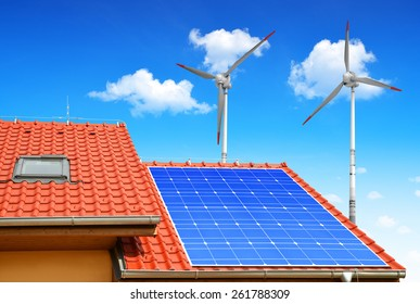 Solar panel on the roof of the house in the background wind turbines.