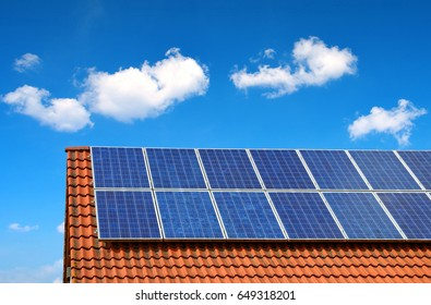 Solar panel on the roof of the house in the background blue sky.
