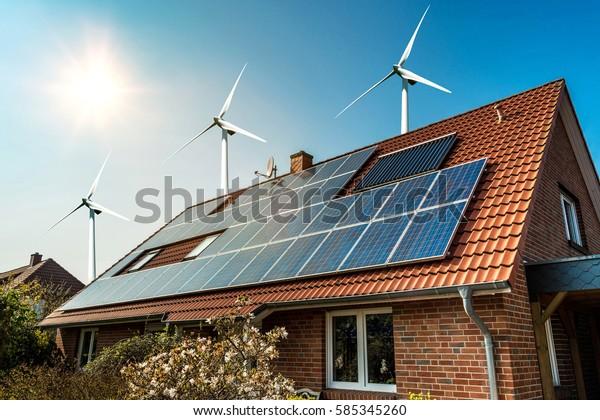 Panel solar en un techo de una casa y turbinas eólicas en torno - concepto de recursos sostenibles