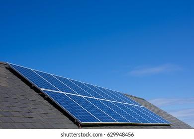 Solar panel on slate roof , blue sky.