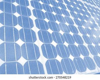 Solar panel photovoltaic cells array close up with blue sky, lens flare copy space, an eco friendly power source which uses the sun to generate clean renewable energy.