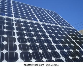 Solar panel photovoltaic cells array close up with blue sky, lens flare copy space, an eco-friendly power source which uses the sun to generate clean renewable energy.