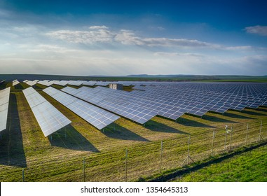 Solar panel produces green, environmentaly friendly energy from the setting sun. Aerial view from drone. Landscape picture of a solar plant that is located inside a valley