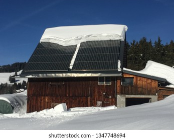 Solar panel roof covered by snow on wooden house in the alps.