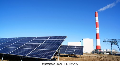 Solar panel, smokestack at power plant