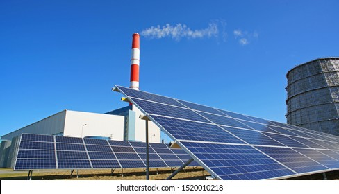Solar panel, smokestack and water cooler at power plant