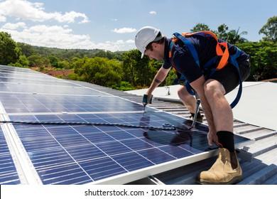 Solarpaneeltechniker mit Bohrmaschine zur Installation von Solarpaneelen auf Dach an sonnigen Tagen