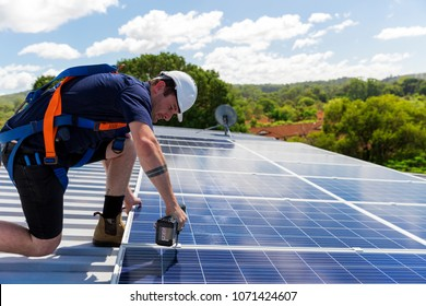 Solar panel technician with drill installing solar panels on roof on a sunny day