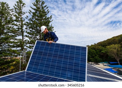 Solar panel technician installing solar panels on roof
