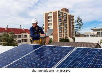 Solar panel technician with laptop on house roof