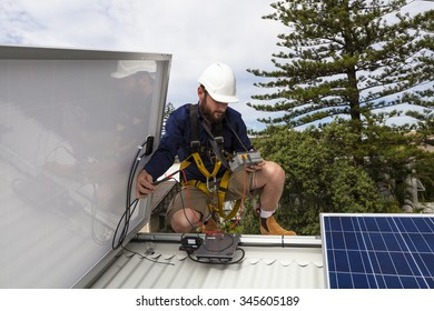 Solar panel technician measuring solar output on roof