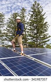 Solar panel technician with safety equipment on roof