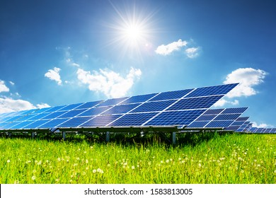 Solar panel under blue sky with sun. Green grass and cloudy sky. Alternative energy concept