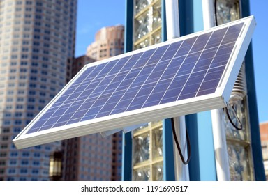Solar panel in urban environment with buildings and skyscrapers in background with blue sky