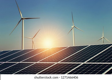 solar panel and wind turbine with sunrise background. concept clean energy