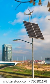 Solar panel and wind turbine under cloudy blue sky on the background of the building and the river bridge in city