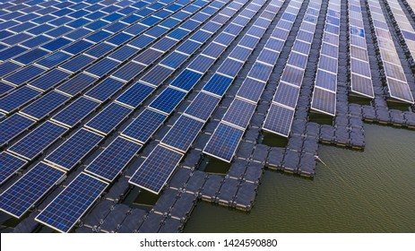 Solar panels in aerial view, rows array of polycrystalline silicon solar cells or photovoltaics in solar power plant floating on the water in lake.