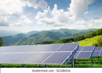 solar panels against mountain landscape against blue sky with clouds