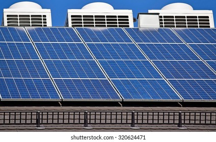 Solar panels and air conditioners on the roof of a building