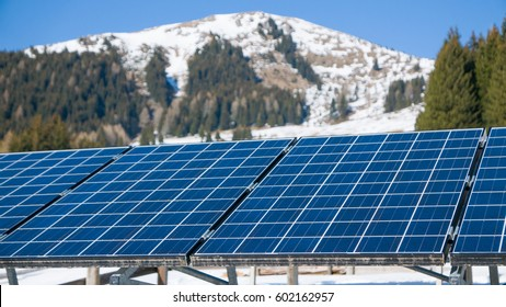 Solar panels background against snowy mountain and blue sky