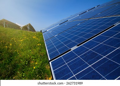 Solar panels, blue sky and green grass in bright sunshine