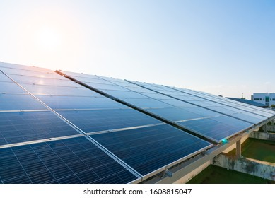 Solar panels and blue sky with light flare background.Solar cells farm on the roof.Photovoltaic modules for renewable energy.Save the earth and the energy with good environment concept.