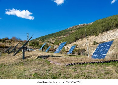 Solar panels with blue sky and mountains in the background.