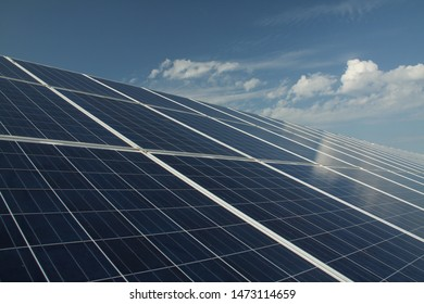 Solar panels with clouds and blue sky in the background