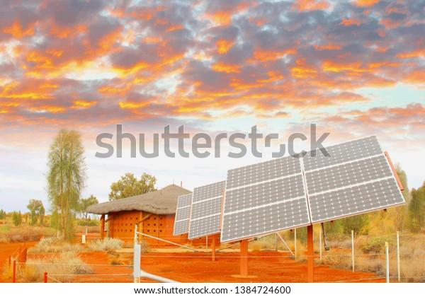 Panneaux solaires dans le désert sous des nuages de ciel colorés au coucher du soleil, production d'énergie solaire en Afrique. Projet d'investissement visant à réduire les émissions de co2