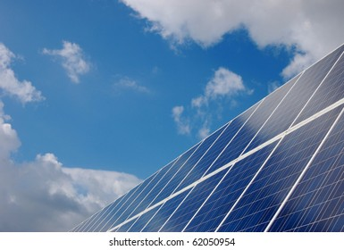 Solar Panels in front of cloudy blue sky