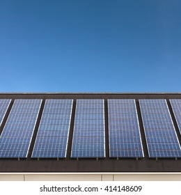 Solar panels in a horizontal row on a roof with a blue sky in the background