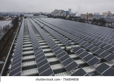 Solar panels installed on a roof of a large industrial building or a warehouse. Industrial buildings in the background. Horizontal photo.