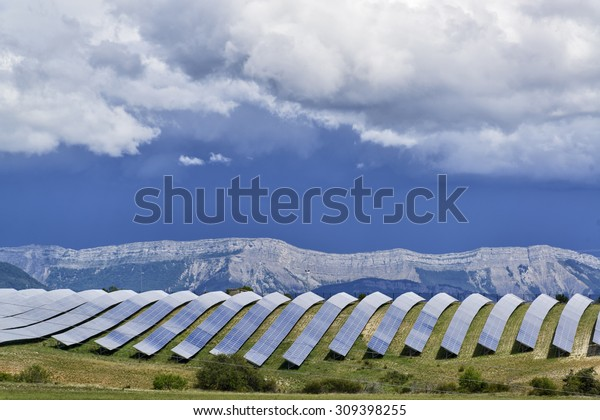 Solar panels lines in the field with big storm cloud in the sky