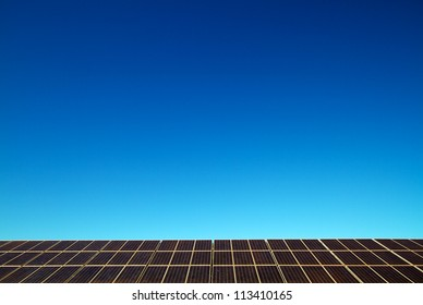Solar panels lining the horizon, blue sky