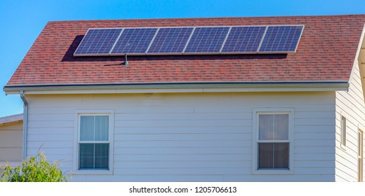 Solar panels mounted on the red rooftop of a home