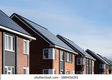 Sonnenkollektoren auf den Dächern einer Reihe moderner Neubauhäuser in Lemmer, Friesland, Niederlande mit blauem Himmel