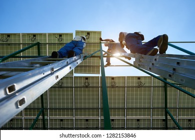 Solar panels mounting work ending by professionals workers team. Using special equipment, providing new technologies ecology saving, green energy solution. High-tech exterior,smart building. Ladder.