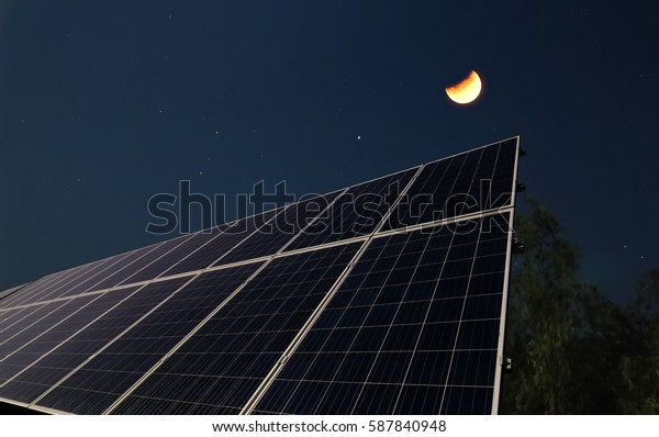 Solar panels at night with the half moon before the sun rising