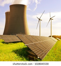 Solar panels, nuclear power plant and wind turbines at sunrise. Energy resources concept.